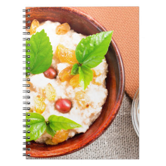 Old wooden bowl of healthy oatmeal with berries notebook