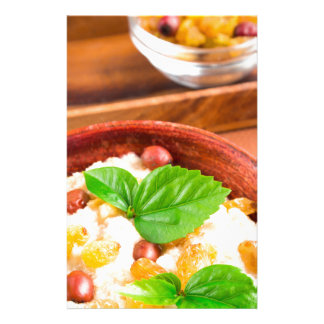 Old wooden bowl of healthy oatmeal with berries stationery