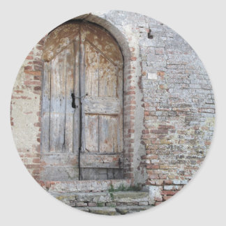 Old wooden door in old brick wall classic round sticker