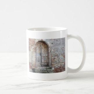 Old wooden door in old brick wall coffee mug
