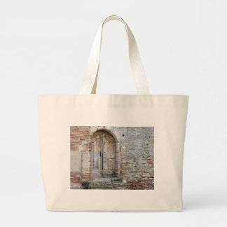Old wooden door in old brick wall large tote bag