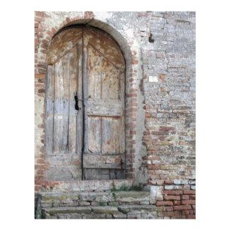 Old wooden door in old brick wall letterhead