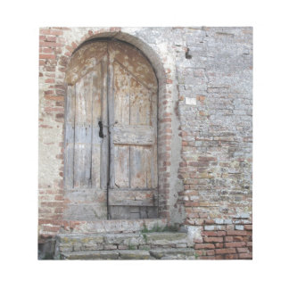 Old wooden door in old brick wall notepad