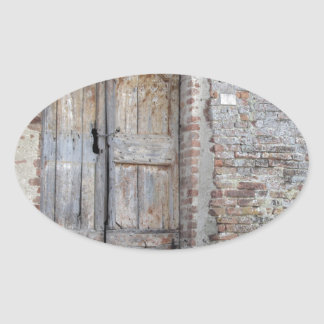 Old wooden door in old brick wall oval sticker