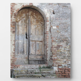 Old wooden door in old brick wall plaque