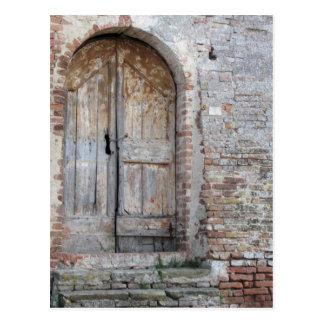 Old wooden door in old brick wall postcard