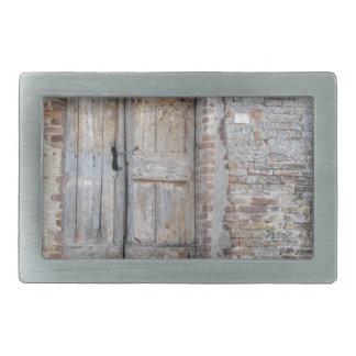 Old wooden door in old brick wall rectangular belt buckles
