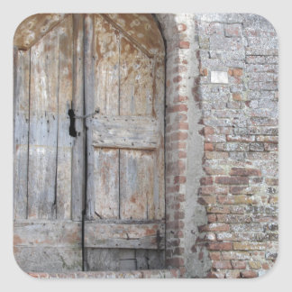 Old wooden door in old brick wall square sticker
