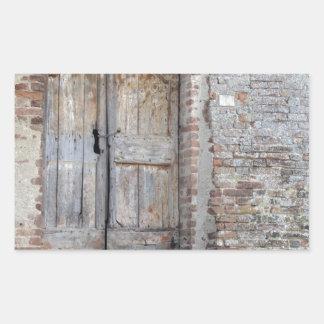 Old wooden door in old brick wall sticker