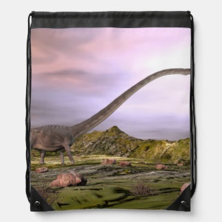 Omeisaurus walking in the desert by sunset drawstring bag