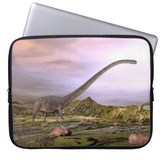 Omeisaurus walking in the desert by sunset laptop sleeve