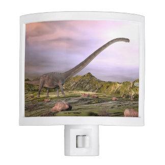 Omeisaurus walking in the desert by sunset night lite