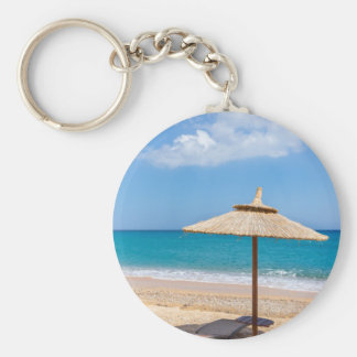 One beach umbrella and sunloungers near ocean keychain
