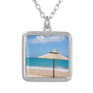 One beach umbrella and sunloungers near ocean silver plated necklace
