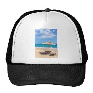 One beach umbrella and sunloungers near ocean trucker hat