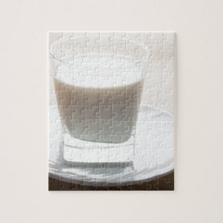 One glass of milk on a white saucer in backlit jigsaw puzzle