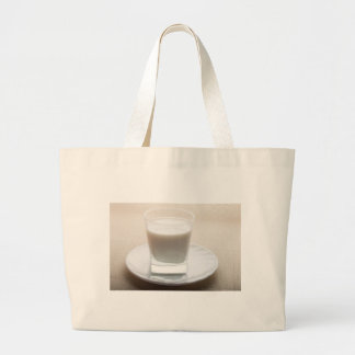 One glass of milk on a white saucer in backlit large tote bag