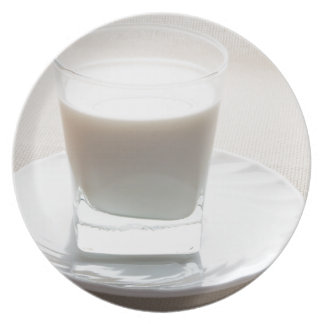One glass of milk on a white saucer in backlit plate