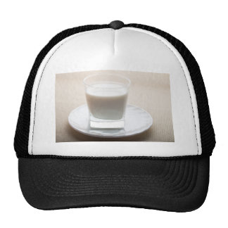 One glass of milk on a white saucer in backlit trucker hat
