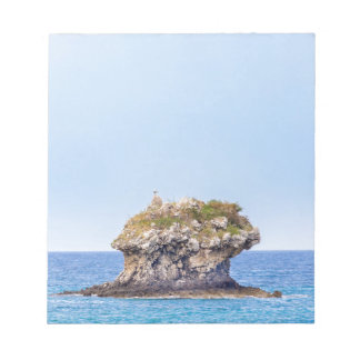 One outstanding rock rising from sea level notepad