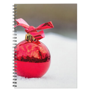 One shiny red christmas ball outside in snow notebooks