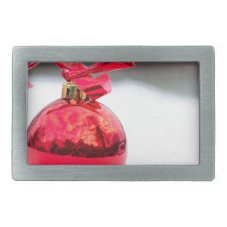 One shiny red christmas ball outside in snow rectangular belt buckles