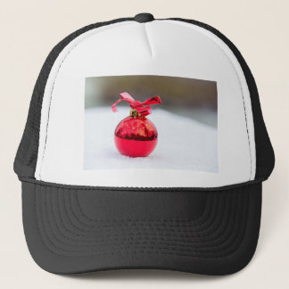 One shiny red christmas ball outside in snow trucker hat