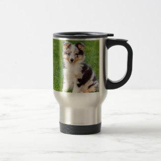 One young sheltie dog sitting on grass travel mug