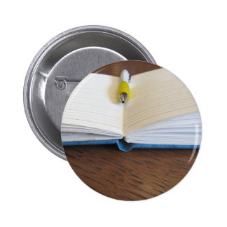 Opened blank lined notebook with pen 2 inch round button