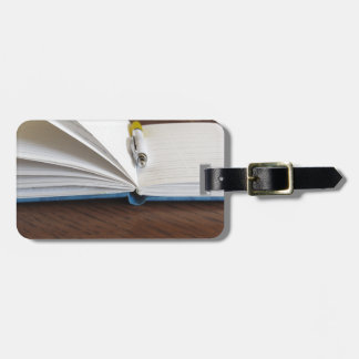Opened blank lined notebook with pen bag tag