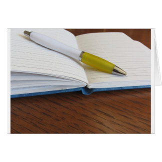 Opened blank lined notebook with pen card