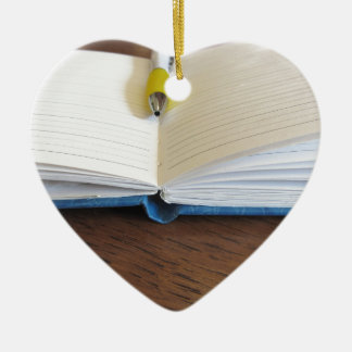 Opened blank lined notebook with pen ceramic heart ornament