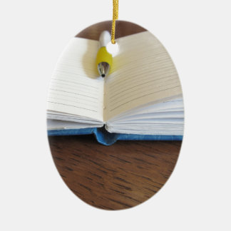 Opened blank lined notebook with pen ceramic oval ornament