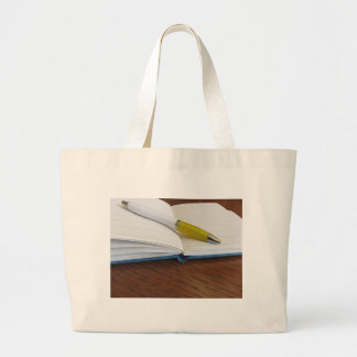 Opened blank lined notebook with pen large tote bag