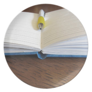 Opened blank lined notebook with pen party plate