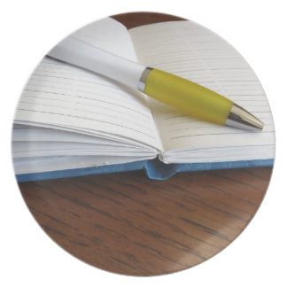 Opened blank lined notebook with pen party plates