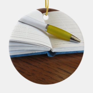 Opened blank lined notebook with pen round ceramic ornament