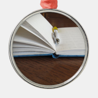 Opened blank lined notebook with pen Silver-Colored round ornament