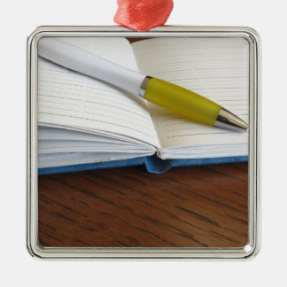Opened blank lined notebook with pen Silver-Colored square ornament