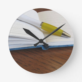 Opened blank lined notebook with pen wallclocks