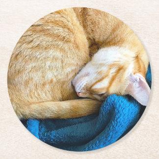 Orange cat curled up on blanket round paper coaster