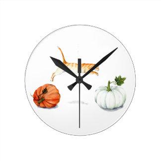 Orange Cat Jumping Between Pumpkins Round Clock