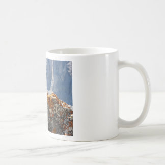 Orange lichens growing on rock face coffee mug