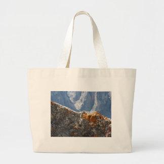 Orange lichens growing on rock face large tote bag