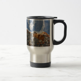 Orange lichens growing on rock face travel mug