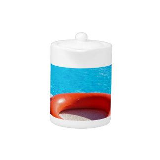 Orange life buoy at blue swimming pool
