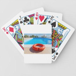 Orange life buoy at blue swimming pool bicycle playing cards