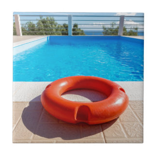 Orange life buoy at blue swimming pool ceramic tiles