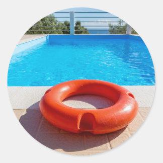 Orange life buoy at blue swimming pool classic round sticker