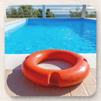 Orange life buoy at blue swimming pool coaster